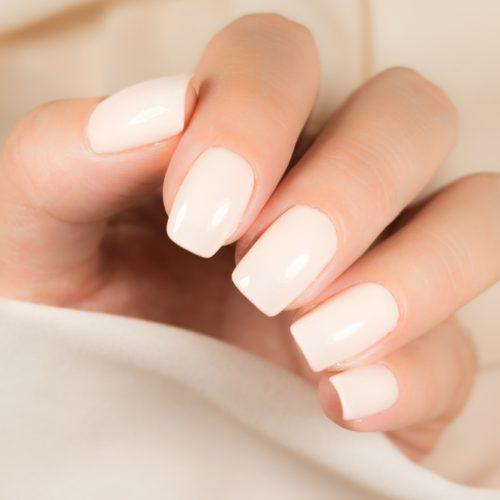 hand med ljusa vita naglar och ljus tröja